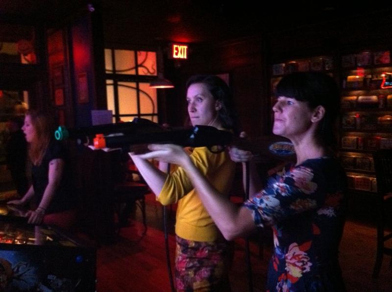 Mary Burke (L) and Jesse Parmentier (R) practice for the Big Buck Hunter World Championship in Manhattan.