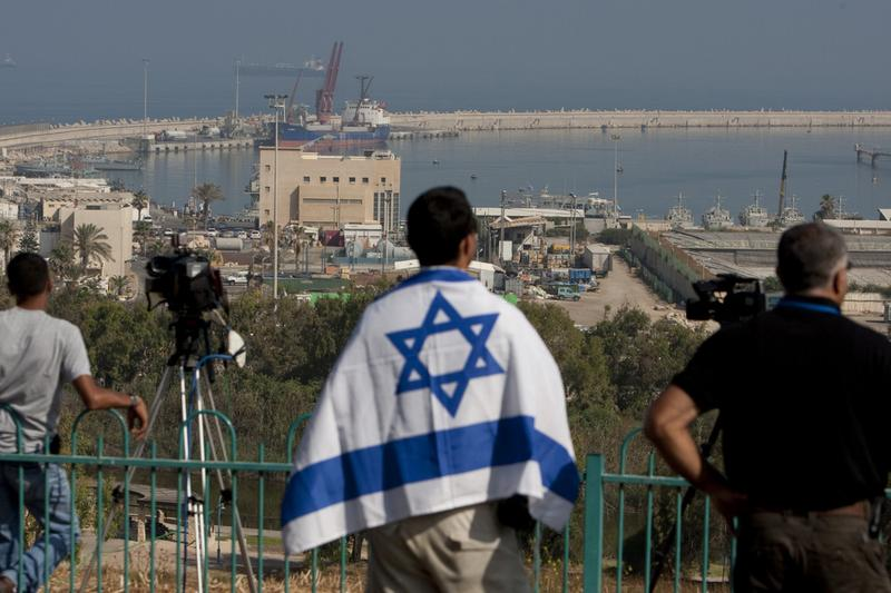 An Israeli man wrapped in the national flag stands next to cameramen at the Israeli army navy port in the southern Israeli town of Ashdod on May 31, 2010.
