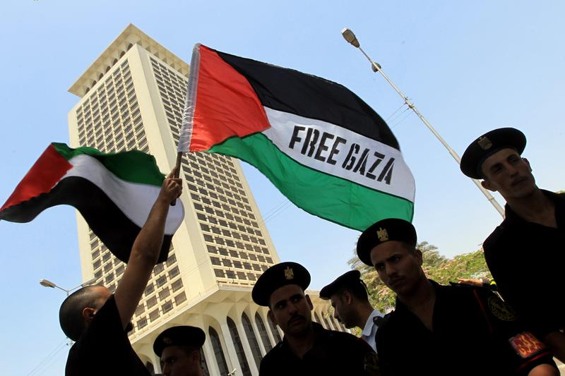 Egyptian protesters wave Palestinian flags with a Free Gaza slogan as they face riot police during a demonstration in front of Foreign Ministry headquarters in Cairo on May 31, 2010.