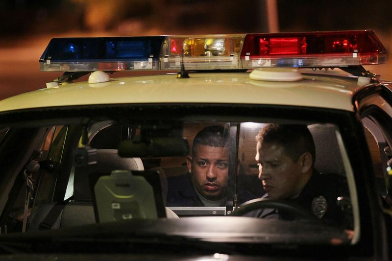 Tucson Police officer Luis Hernandez questions a suspect following a fight June 3, 2010 in Tucson, Arizona. Tucson is gearing up to begin training its officers on the implementation of SB 1070.