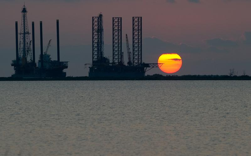 The sun sets behind two under-construction offshore oil platform rigs in Port Fourchon, La, June 14, 2010, as cleanup of the BP Deepwater Horizon oil continues.
