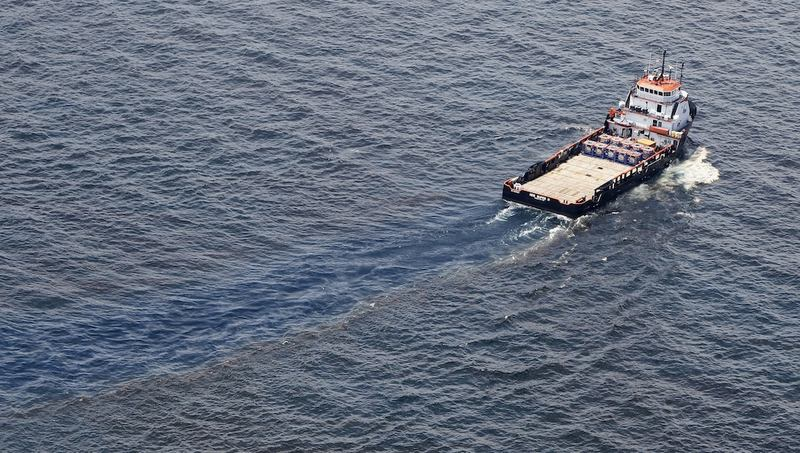 A ship passes through oil covered water near the site of the Deepwater Horizon oil spill on June 19, 2010 in the Gulf of Mexico off the coast of Louisiana.