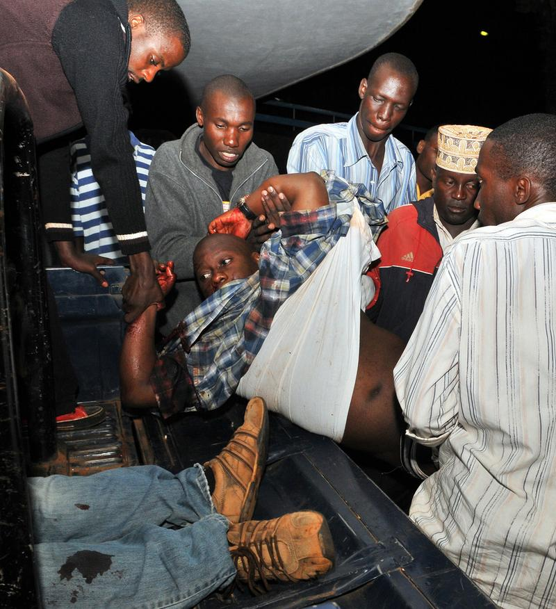 People carry an injured man in Kampala's Mulago hospital, on July 12, 2010 after twin bomb blasts tore through crowds of football fans watching the World Cup final, killing 64 people.