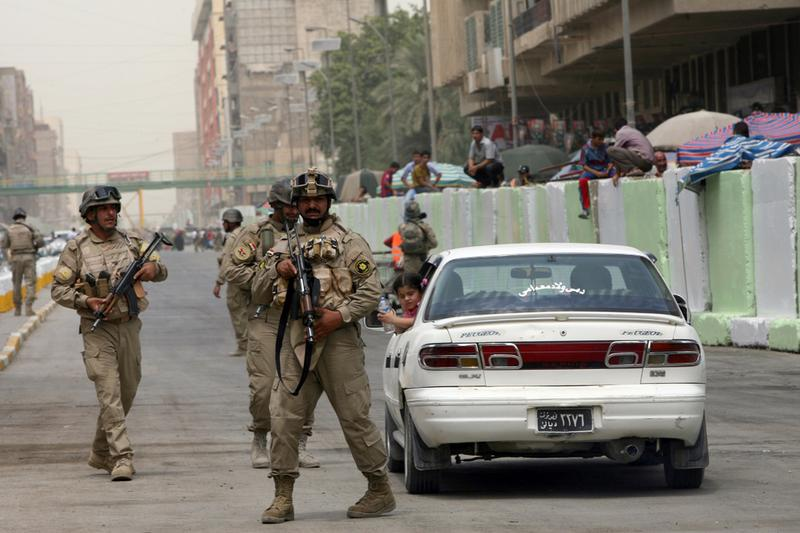 Iraqi soldiers are deployed while reopening al-Jumhuri street by Shorja market in the center of Baghdad on July 31, 2010.