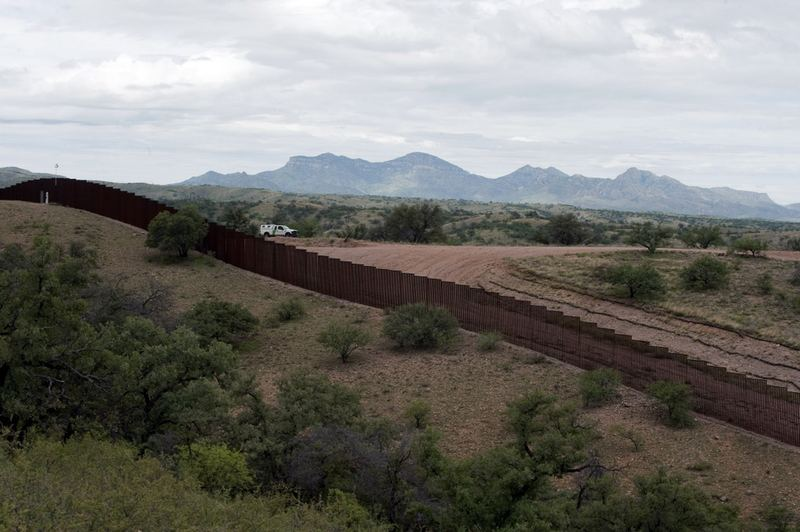 A US Border Patrol vehicle drives along the fence separating the US from Mexico, near the town of Nogales, Sonora, Mexico, on July 31, 2010.
