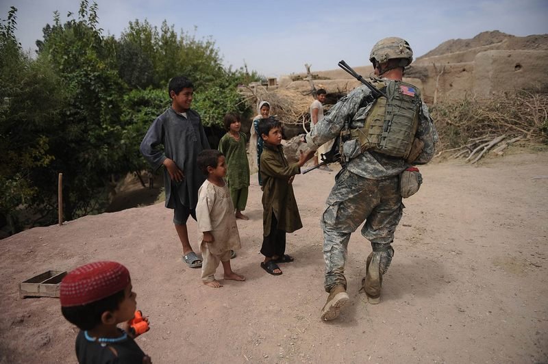 US Staff Sergeant Josh Middlebrook of Charlie Company 2-508 PIR Second Platoon of the Second BTC, 101st ABN Div. greets Afghan children during a joint patrol with Afghan National Security Forces.