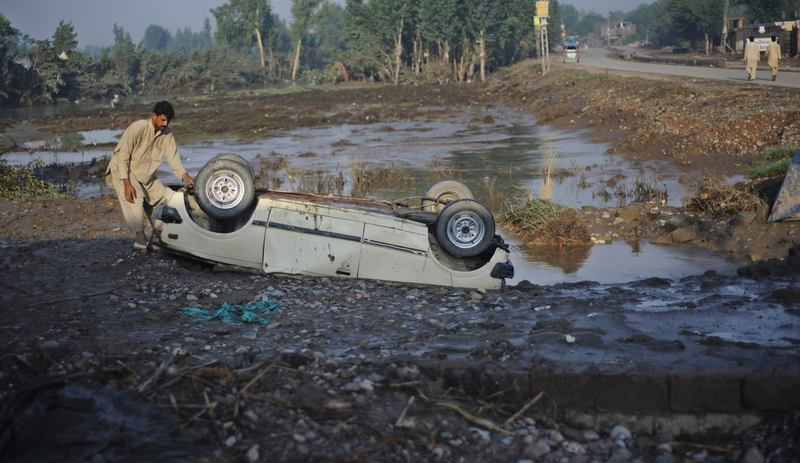 A Pakistani flood survivor inspects an overturned car in Charsadda on August 4, 2010. Devastating floods have swept away farmland and devastated livestock in Pakistan's northwest.