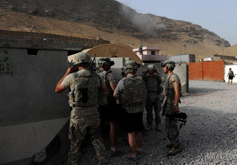 US soldiers gather at the entrance of an anti-mortar shell shelter as smoke rises at the impact site of a mortar shell during an attack on the US base in Kandahar province on August 12, 2010