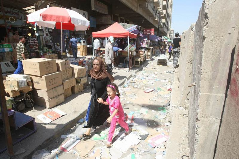 A child cries as she runs with her mother following a nearby double suicide bombing in which some twelve people were killed on September 05, 2010, at an Iraqi Defence ministry complex.