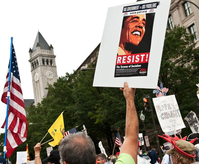 A demonstrator carries a sign calling people to 'resist' US President Barack Obama perceived socialist policies during a march of supporters of the conservative Tea Party movement in Washington.