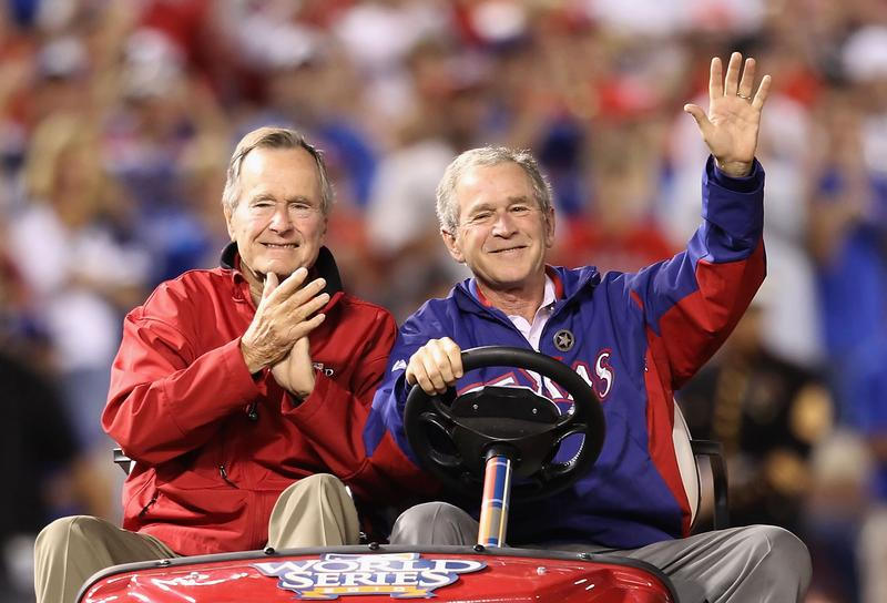 Former President George W. Bush and his father Former President George H.W. Bush wave to the crowd before a Texas Rangers World Series game in October 2010.