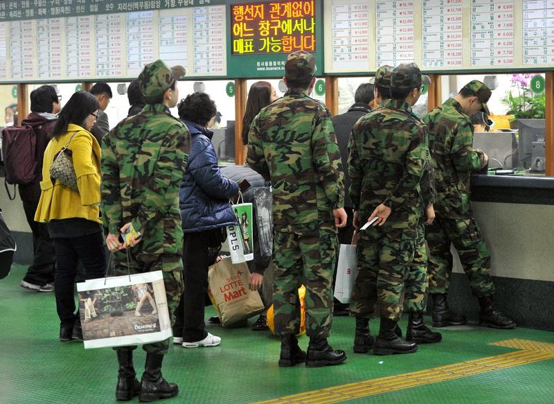 South Korean soldiers gather to return their military unit at a bus terminal in Seoul on November 23, 2010.