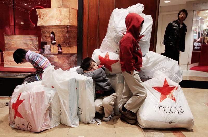 Children wait with shopping bags inside Macy's department store on 'Black Friday.'
