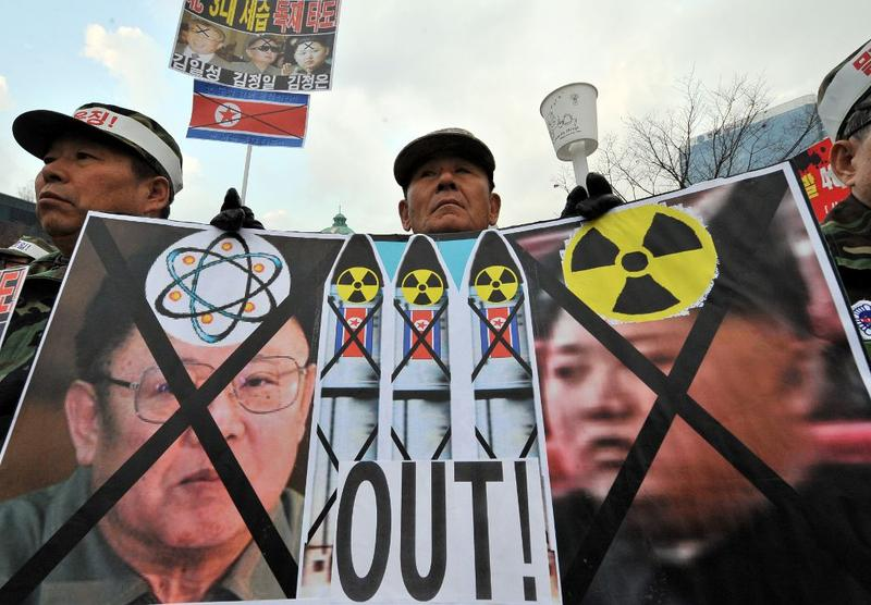 A South Korean veteran holds a placard showing North Korean flags and portraits of Kim Jong-Il (L) and his son Jong-Un (R) during a rally in Seoul on December 2, 2010