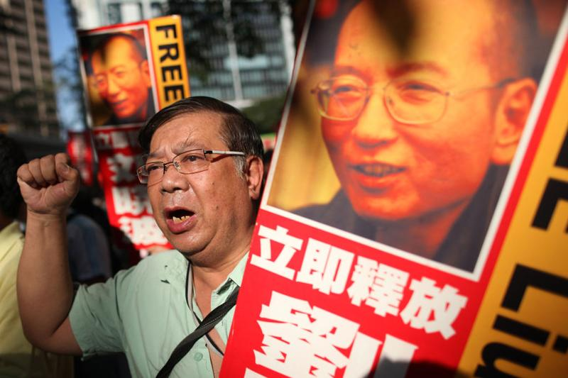 Protesters wave banners and placards as they march through Hong Kong on December 5, 2010, calling for the release of jailed Chinese Nobel Peace Prize winner Liu Xiaobo.