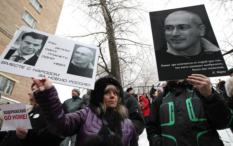 Supporters of Yukos oil company chief executive officer Mikhail Khodorkovsky hold his portraits and posters outside a Moscow court, on December 27, 2010.