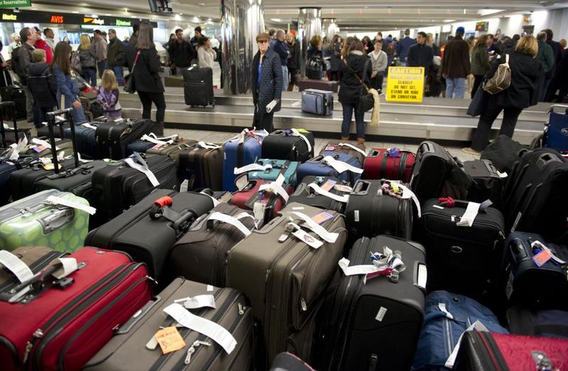 Unclaimed bags in the foreground as travelers retrieve their luggage at New York's LaGuardia Airport on December 28, 2010.