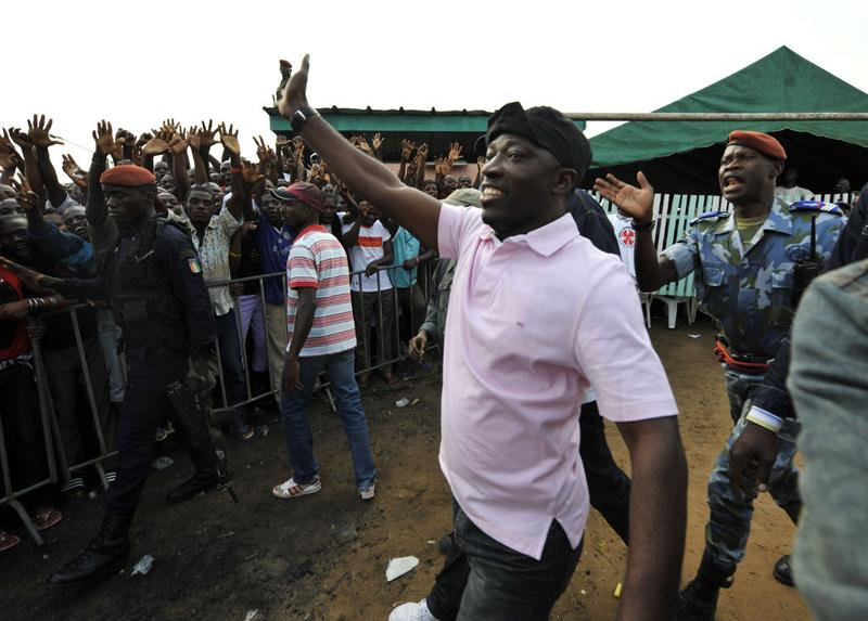 """Charles Ble Goude, Ivory Coast strongman Laurent Gbagbo's most notorious street lieutenant and leader of the """"Young Patriots,"""" waves as he greets crowds in Abidjan on December 29, 2010."""