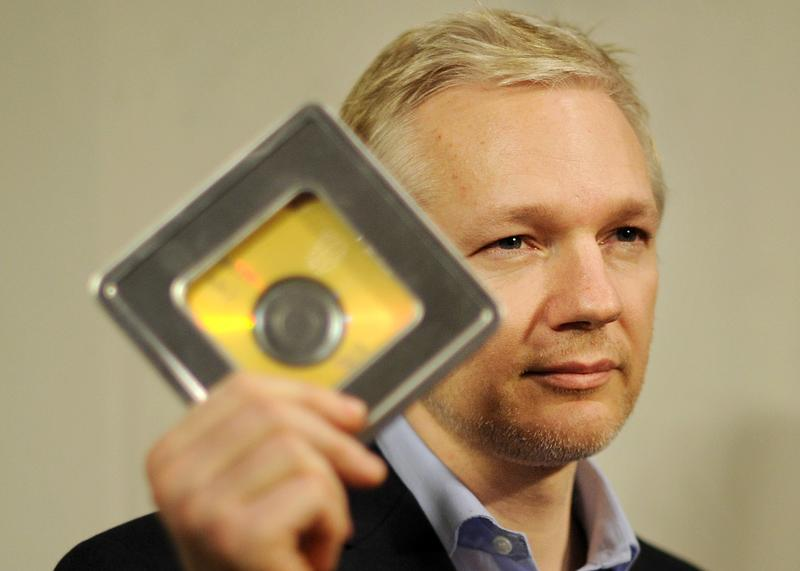 Julian Assange holds a CD containing data given to him by former Swiss banker Rudolf Elmer, following a press conference in London, on January 17, 2011.