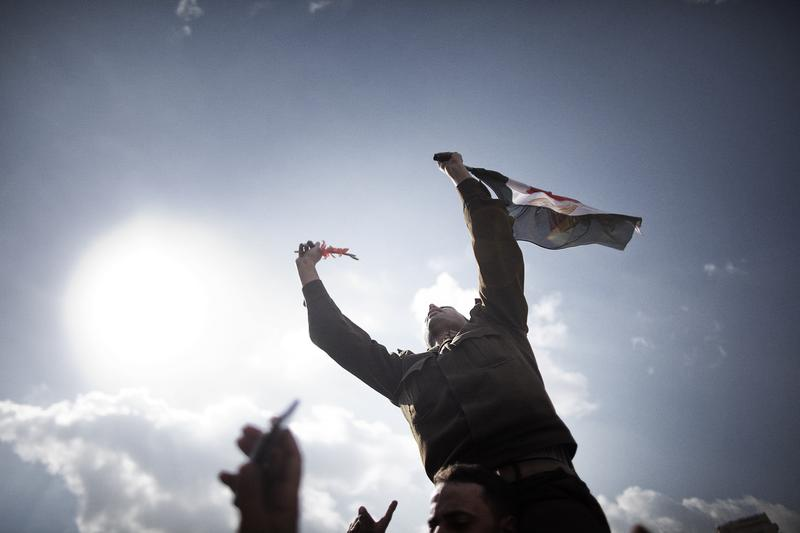 An Egyptian army Captain identified as Ihab Fathi holds the national flag while being carried by demonstrators during a protest in Tahrir Square in Cairo on January 31, 2011.