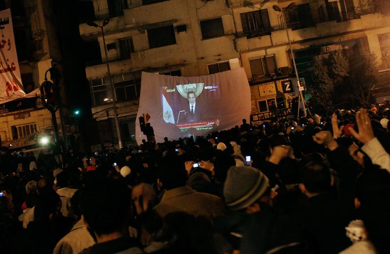 Protesters watch Egyptian president Hosni Mubarek give a speech on a projected television screen in Tahrir Square February 1, 2011 in Cairo, Egypt.