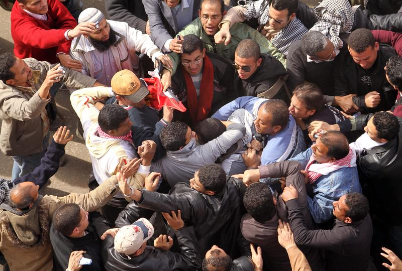 Egyptian protestors opposed to President Hosni Mubarak detain a government supporter during protests on February 3, 2011 near Cairo''s central Tahrir Square.