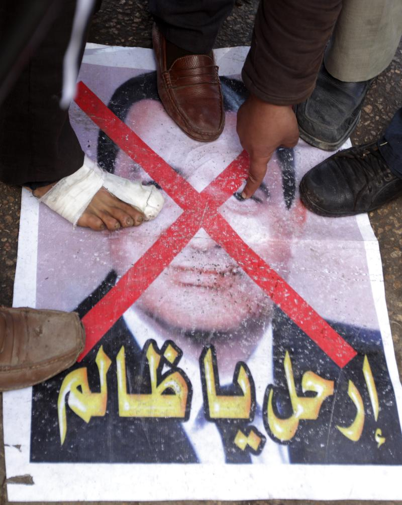 Egyptian anti-government protesters step on a picture of President Hosni Mubarak in Cairo's Tahrir Square on February 06, 2011.