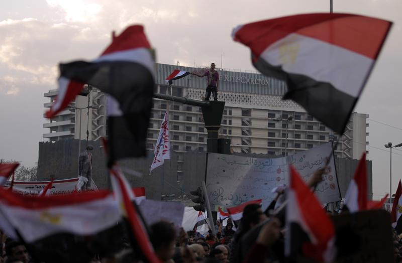 Egyptian anti-government demonstrators wave their national flag as they gather at Cairo's Tahrir Square on February 6, 2011 on the 13th day of protests calling for the ouster of President Mubarak.