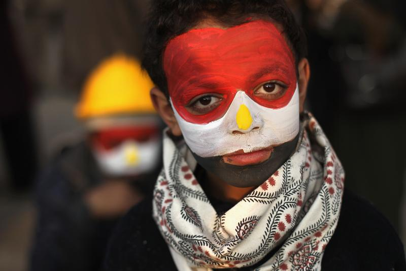 His face painted in the national colors, anti-government protester Mamoud Tariq, 13, attends a demonstration in Tahrir Square on February 7, 2011 in Cairo, Egypt.