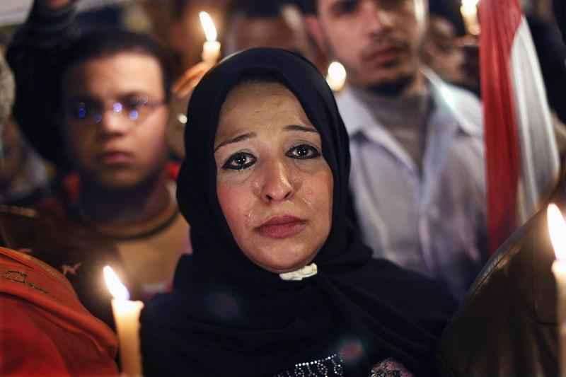A woman cries as anti-government protesters walk during a candlelight vigil for those killed on February 9, 2011 in Cairo, Egypt.