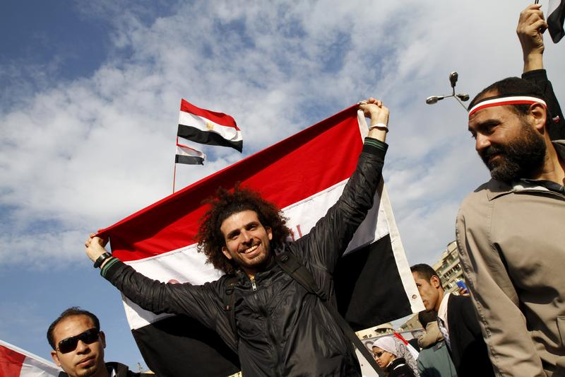Egyptian anti-government demonstrators hold their national flag as they gather at Cairo's Tahrir Square on February 10, 2011.