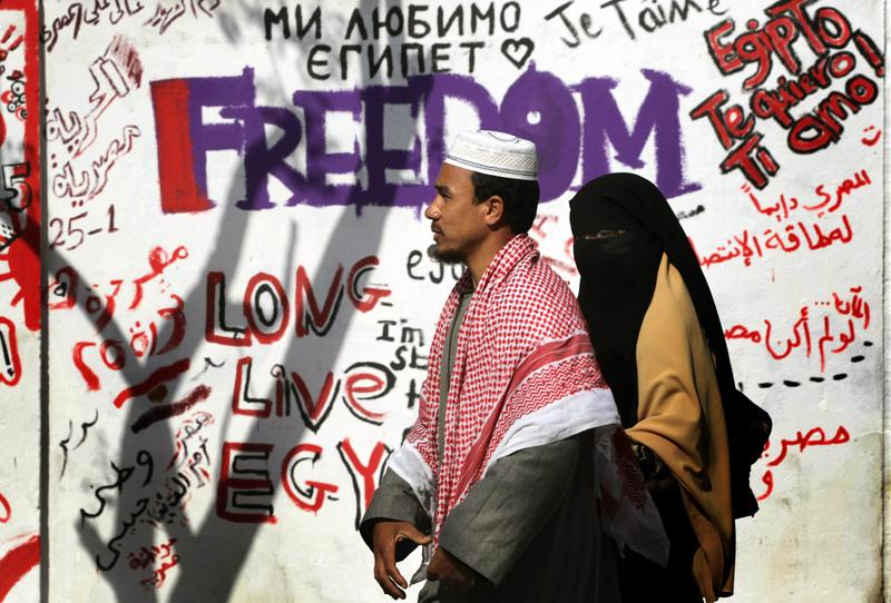 Egyptians walk past revolutionary graffiti on February 13, 2011 in Cairo, Egypt. Two days after the resignation of President Hosni Mubarak