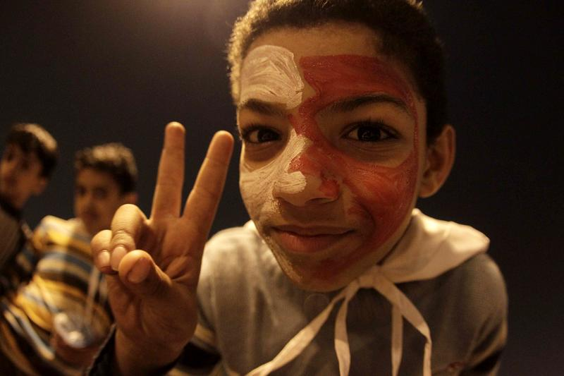 A Bahraini boy with his face painted in the colours of his national flag flashes the victory sign as he takes part in a demonstration calling for a regime change at Pearl Square in Manama, Bahrain.