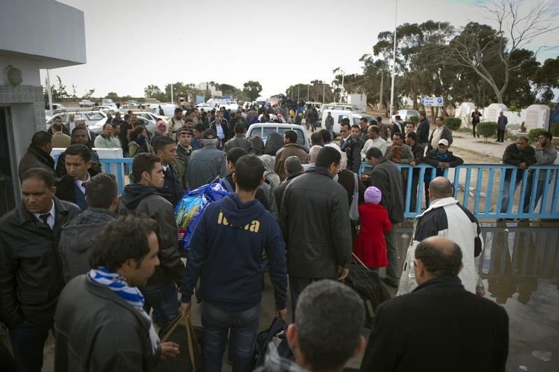 Tunisians working and living in Libya arrive on February 22, 2011 at the Ras Jdir border post (in the background), near the Tunisian city of Ben Guerdane after they fled Libya.