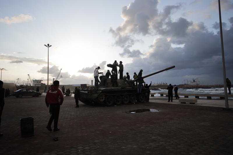 Libyans stand atop an army tank outside the court house in the eastern dissident-held city of Benghazi on February 24, 2011 amid political turmoil and an insurrection against Moammar Gadhafi's regime.