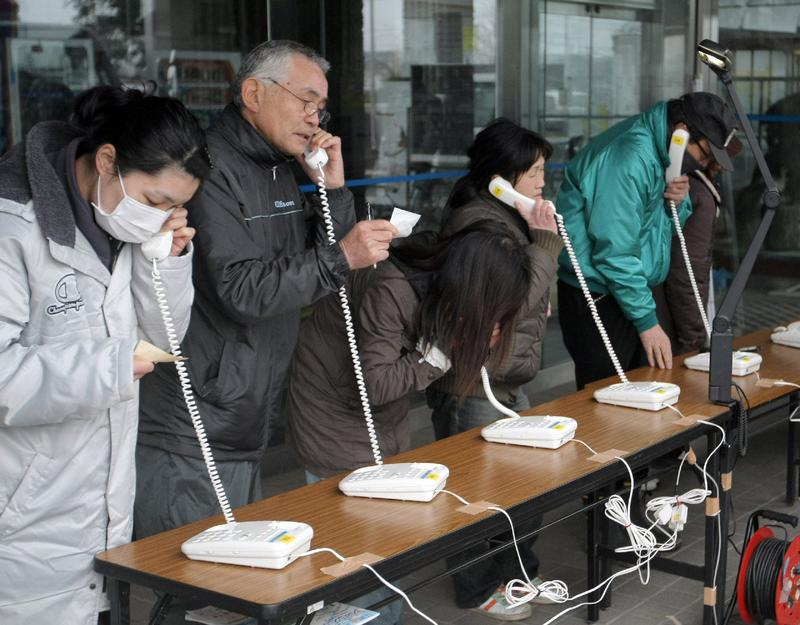 Evacuees use temporary public telephones set up in Yamada, Iwate prefecture, on March 15, 2011.