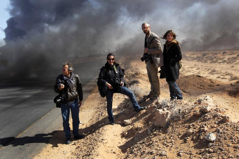 Yuri Kosyrev of Time Magazine, Lynsey Addario and Tyler Hicks of the New York Times and freelancer Nicki Sobecki stand during a pause in the fighting March 11, 2011 in Ras Lanuf, Libya.