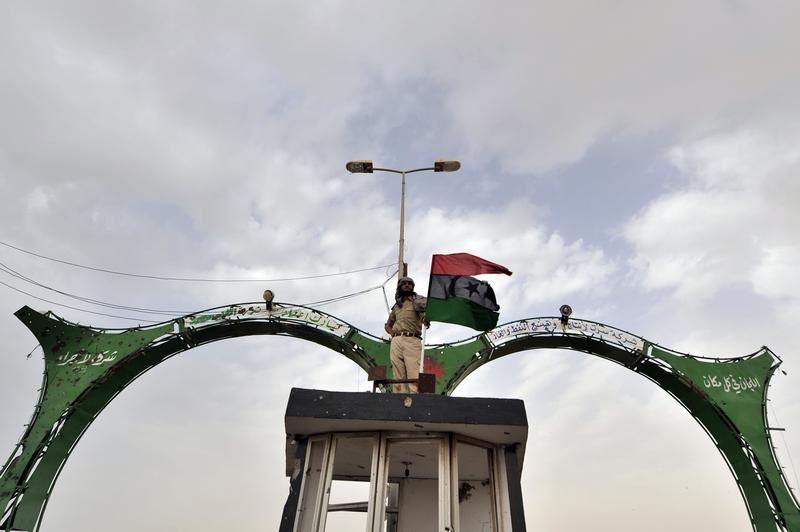 A Libyan rebel holds his country's former national flag as he stands at the west gate of the eastern city of Ajdabiya on March 30, 2011.