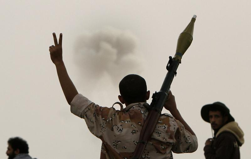 A Libyan rebel walking with a rocket-propelled grenade (RPG) flashes the victory sign as smoke billows from a distance in the eastern city of Ajdabiya on March 30, 2011.