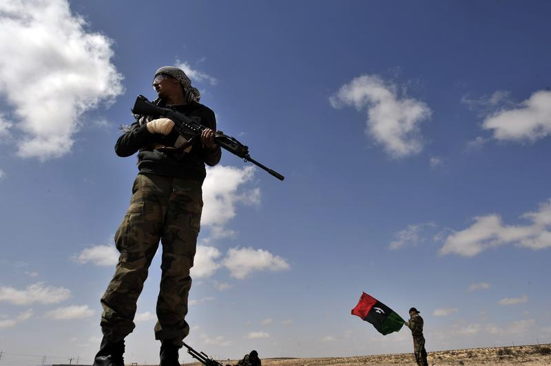 Libyan anti-Kadhafi fighters stand guard on a desert road some 30 kilometers before the eastern town of Brega on March 31, 2011.