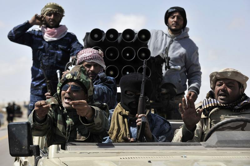 Libyan anti-Gadafi fighters return from battle some 30 kilometers before the eastern town of Brega on March 31, 2011.