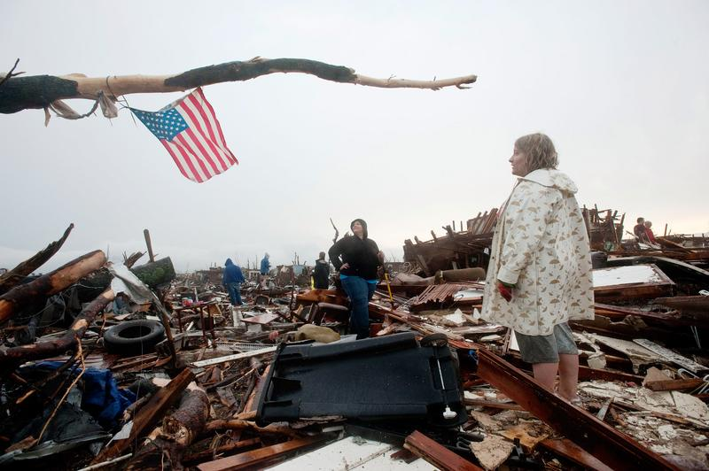 Sheila Bolte (L) and Ashley Hailey look up at the American flag they placed in a tree branch over the remains of Ashley's home after a tornado on May 23, 2011 in Joplin, Missouri.