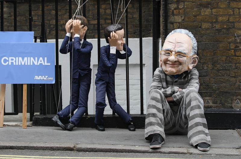 A protester wearing a Rupert Murdoch mask demonstrates with David Cameron and Nick Clegg puppets outside the apartment of the News Corp CEO on July 13, 2011 in London, England.