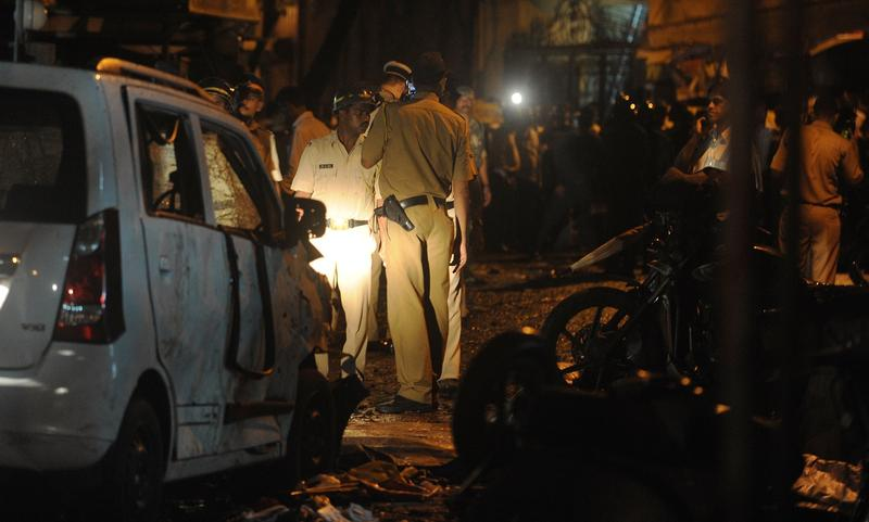 Police officials inspect a bomb blast site at the Opera house area in Mumbai on July 13, 2011.