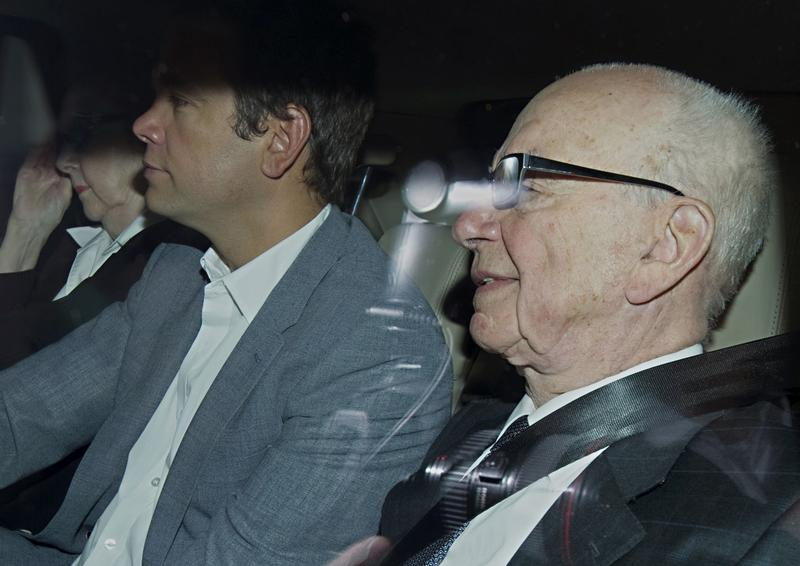 News Corporation Chief Rupert Murdoch (R) and his son Lachlan (C) are pictured through a car window as they leave Rupert Murdoch's London home, on July 14, 2011.