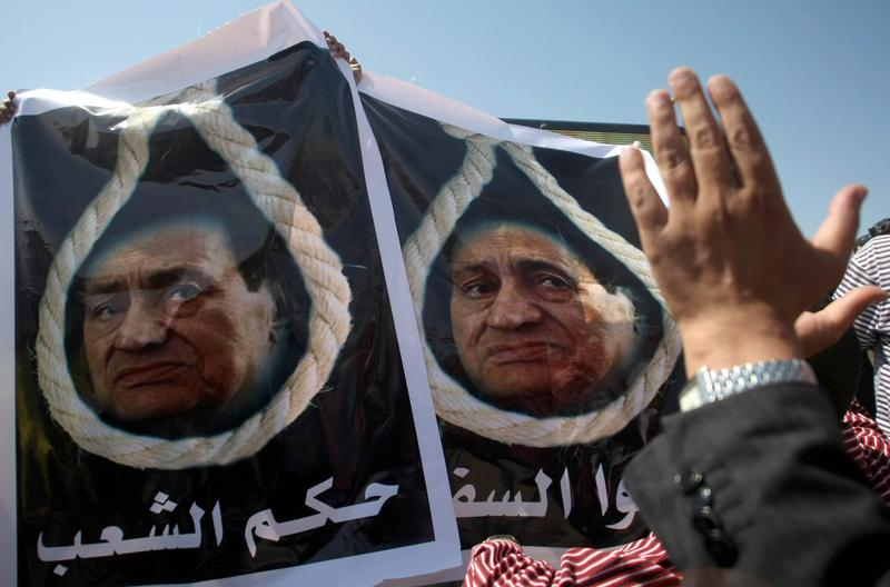 Egyptians carry posters showing Hosni Mubarak behind a noose outside the court for his trial and that of his two sons August 3, 2011.