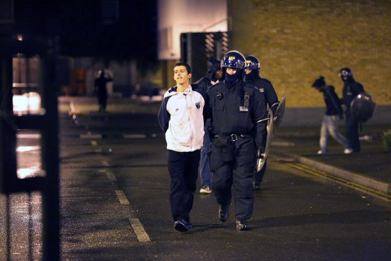 Two young men are detained outside the Currys electrical store in Brixton on August 8, 2011 in London, England. Widespread rioting and looting took place across many parts of London on Monday.