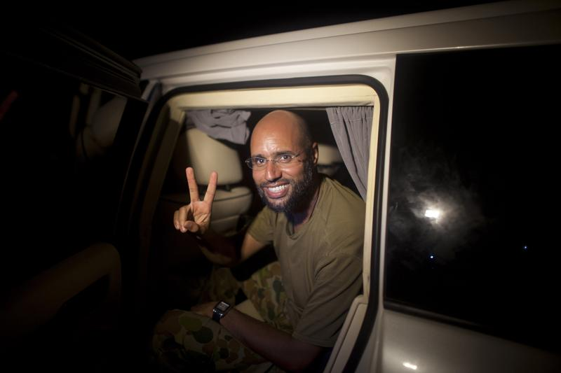 Seif al-Islam Gadhafi, son of Libyan leader Moammar Gadhafi,  flashes the V-sign for victory as he appears in front of supporters and journalists in the Libyan capital Tripoli on August 23, 2011.