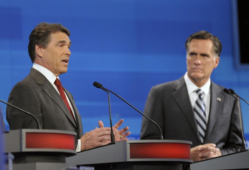 Republican presidential candidates, Texas Gov. Rick Perry (L) speaks as former Massachusetts Gov. Mitt Romney listens in the Fox News/Google GOP Debate on September 22, 2011 in Orlando, Florida.