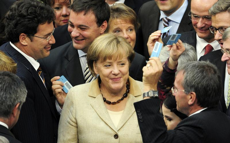 German Chancellor Angela Merkel (C) smiles surrounded by MPs holding their ballots on September 29, 2011 at the Lower House of German Parliament in Berlin.